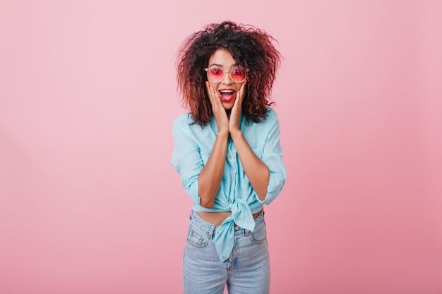 驚きの感情を表現する巻き毛の髪型でショックを受けたアフリカの女性。彼女の顔に触れているデニムパンツの驚くべきスポーティな黒人女性の屋内の肖像画。 無料写真