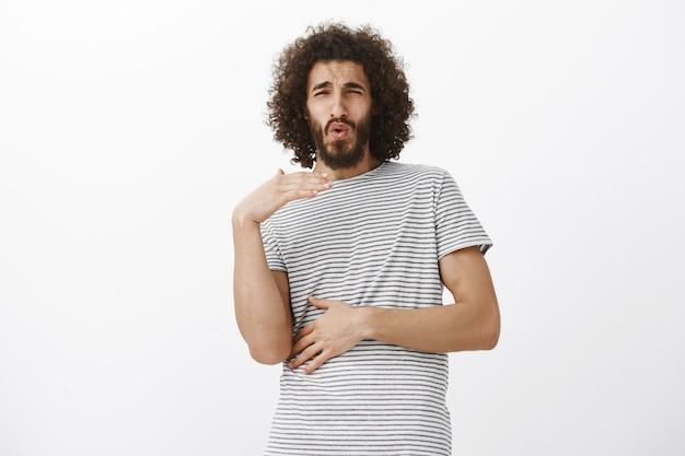 Шокированный изумленный восточный парень с бородой, машет ладонью и хмурится Бесплатные Фотографии
