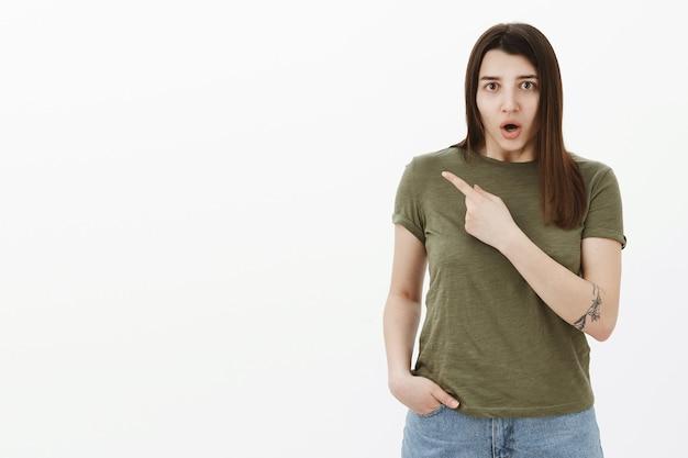ショックを受けて混乱している神経質な少女が欲求不満で口をあけて、左上隅を指差して質問し、灰色の壁を心配して心配そうな不安な表情で何が起こったのか尋ねた 無料写真