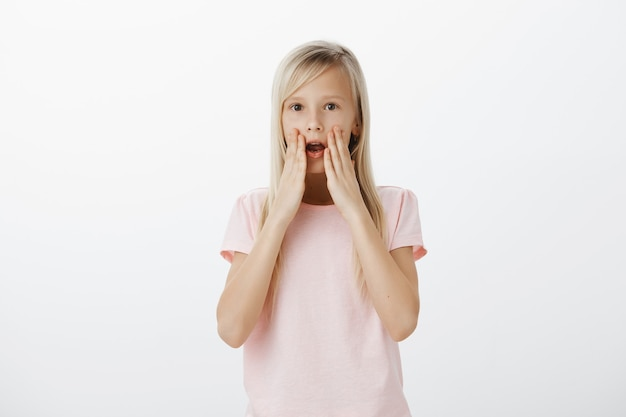 Шокированная и впечатленная маленькая блондинка задыхаясь, удивленная отвисшая челюсть Бесплатные Фотографии