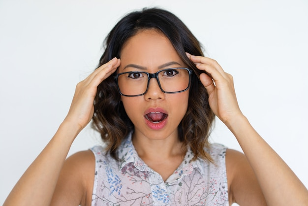 Shocked asian girl extremely surprised with news Free Photo