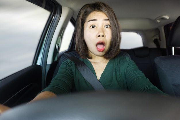 Shocked asian woman driving car cause of accident Premium Photo