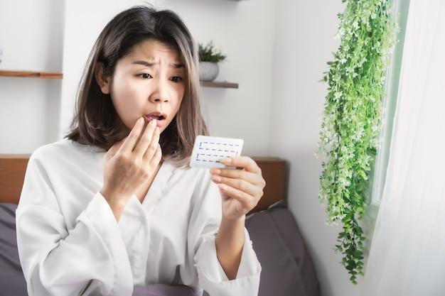 Шокированная азиатская женщина забыла принять противозачаточные таблетки Premium Фотографии