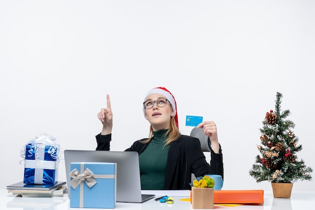 Shocked attractive woman with santa claus hat and wearing eyeglasses sitting at a table christmas gift and holding bank card pointing above in the office Free Photo