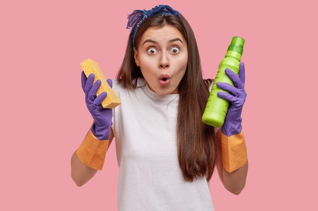 Giovane femmina attraente scioccata dal servizio di pulizia, tiene la spugna e il detersivo, mantiene la mascella aperta Foto Gratuite