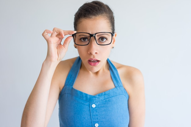 Shocked attractive young woman adjusting eyeglasses and looking at camera. Free Photo