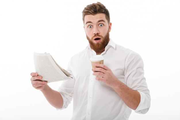 Shocked bearded man in business clothes holding newspaper Free Photo