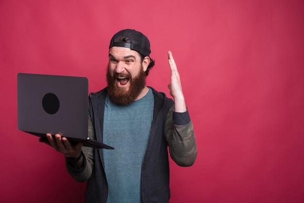 Шокирован бородатый мужчина смотрит на свой ноутбук на розовом фоне. Premium Фотографии