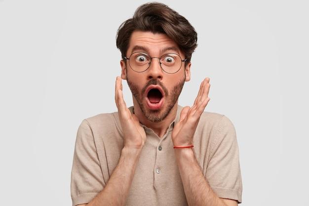 ショックを受けたひげを生やした男は、友人から予期しないニュースを受け取り、顔の近くで手を握りしめ、口を大きく開き、驚きを表現し、白い壁に隔離されます 無料写真