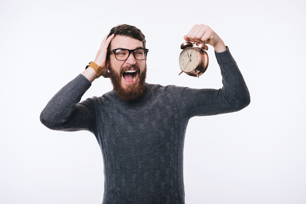 Shocked bearded man in sweater looking at alarm watch Premium Photo