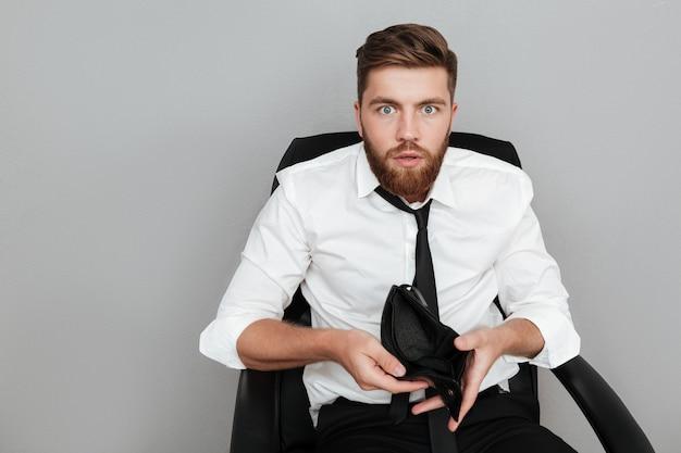 Uomo barbuto colpito in camicia bianca che mostra portafoglio vuoto Foto Gratuite