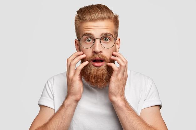 Шокированный бородатый рыжеволосый мужчина с ошеломленным выражением лица смотрит прямо в камеру, держит руки возле щек Бесплатные Фотографии