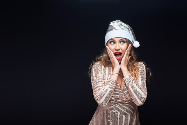 Shocked beautiful woman in dress and santa claus hat isolated on black . Premium Photo