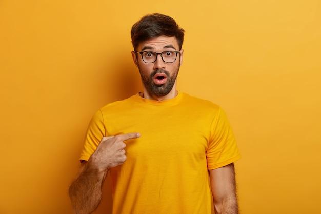 Un uomo sconcertato dalla folta barba, indica se stesso Foto Gratuite