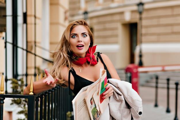 新聞を保持している最新のニュースを議論するショックを受けた金髪の女性 無料写真