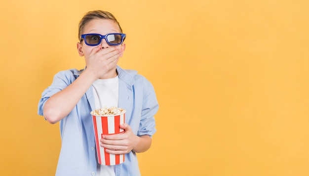 Shocked boy wearing 3d glasses holding popcorn bucket in hand standing against yellow backdrop Free Photo