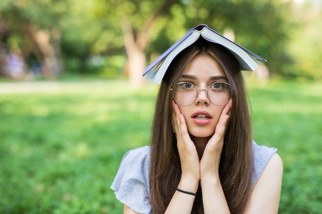 頬に腕を持ってカメラを見ながら、頭に本を持って公園に座っているショックを受けたブルネットの女性 無料写真