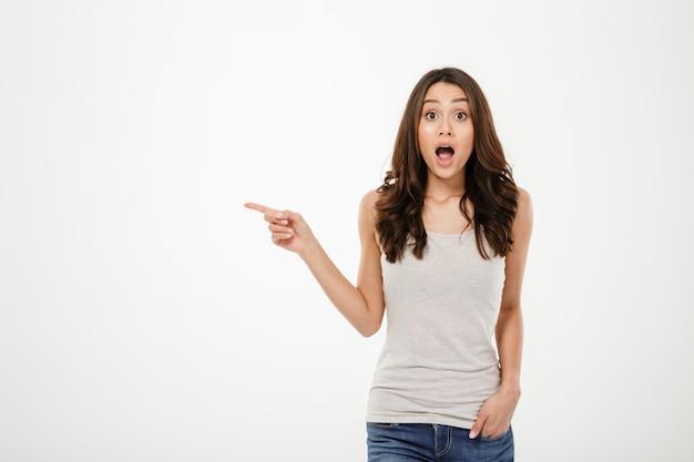 Шокирован брюнетка женщина с рукой в кармане, указывая на copyspace и глядя на камеру над серым Бесплатные Фотографии