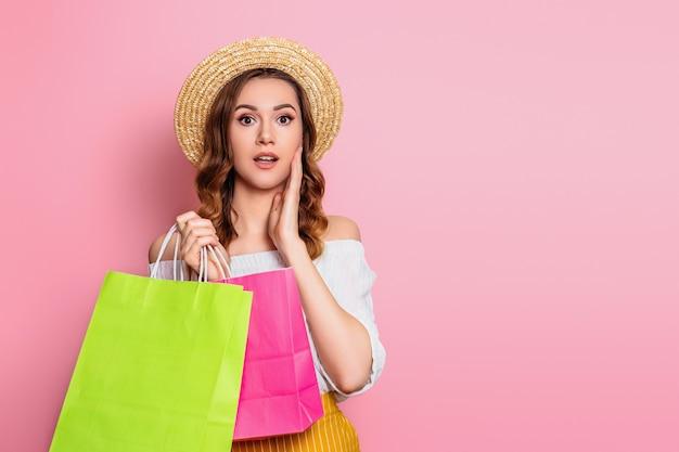 밀 짚 모자와 흰색 드레스에 충격 된 백인 여자 핑크 벽에 고립 된 손에 쇼핑백을 보유하고있다. 놀란 된 흥분된 여자 온라인 쇼핑 웹 배너 판매 개념 프리미엄 사진
