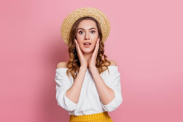 밀 짚 모자와 핑크 벽에 고립 된 화이트 빈티지 드레스에 충격 된 백인 여자. 놀란 된 흥분된 여자 웹 배너 판매 개념 프리미엄 사진