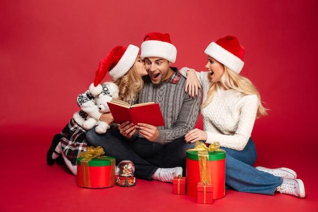 本を読んでクリスマス帽子をかぶってショックを受けた陽気な若い家族。 無料写真