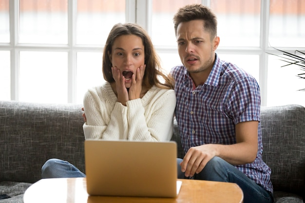 Shocked couple confused and scared watching horror movie on laptop Free Photo