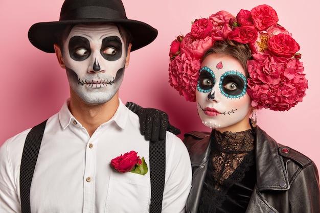 ショックを受けたカップルは怖い表情、ファンキーなメイクや衣装を持っており、赤い花で飾られた黒と白の服を着て、ピンクの壁に対してスタジオで一緒にポーズをとる 無料写真
