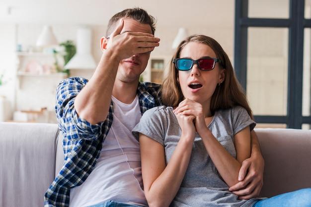 Coppia scioccata guardando film e abbracci sul divano Foto Gratuite