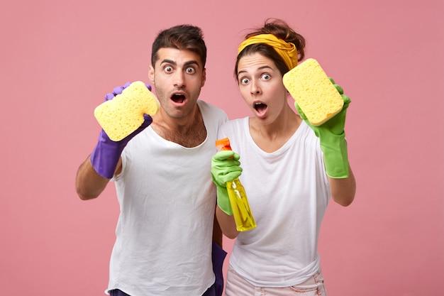 Потрясенная пара с губками и моющим средством для мытья окон. мужчина и женщина из службы уборки оделись небрежно и удивились, увидев много работы. люди, работа, ведение домашнего хозяйства и домашняя концепция Бесплатные Фотографии