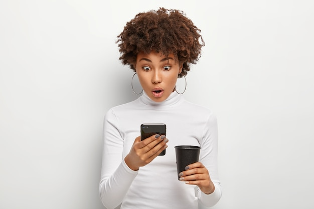 Потрясенная кудрявая молодая женщина реагирует на сообщение, читает плохие новости, держит в руках современный сотовый, пьет кофе на вынос, носит белую удобную одежду, позирует. концепция современных технологий Бесплатные Фотографии