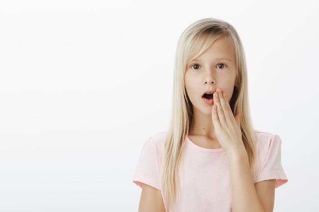 金髪のショックを受けたかわいいヨーロッパの女の子、教室で噂や噂話を広め、他の誰にも秘密が聞こえないように口の近くで手のひらを握り、灰色の壁の上に真剣に立っています 無料写真