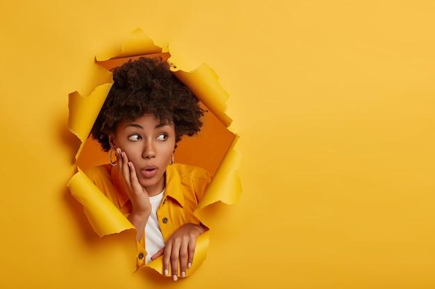 충격을받은 어두운 피부의 여성 모델은 당황스러워 보이고, 광대뼈에 손바닥을 잡고, 큰 할인에 놀라고, 세련된 옷을 입고, 종이 구멍에 포즈, 노란색 스튜디오 배경 무료 사진