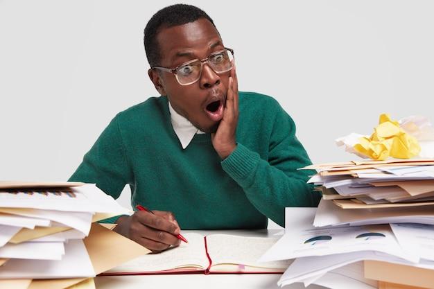 ショックを受けた暗い肌の男は、顎を落とし続け、文書のチャートを見つめ、透明な大きな眼鏡をかけ、低所得で愚痴をこぼします 無料写真