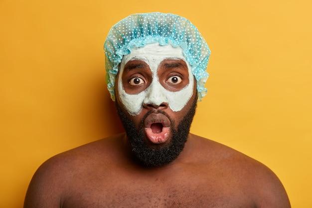 Шокированный темнокожий небритый парень носит глиняную маску на лице, шапочку для ванны, смотрит в камеру с выпученными глазами, проходит косметические процедуры. концепция ухода за кожей Бесплатные Фотографии