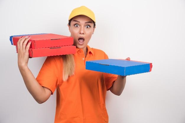 ピザの箱を持っているショックを受けた配達の女性。 無料写真