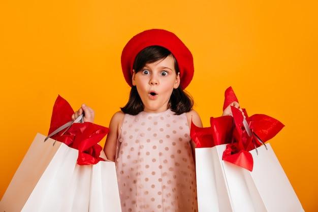 買い物の後にポーズをとってショックを受けたヨーロッパの子供。口を開けて店のバッグを持っている子供。 無料写真