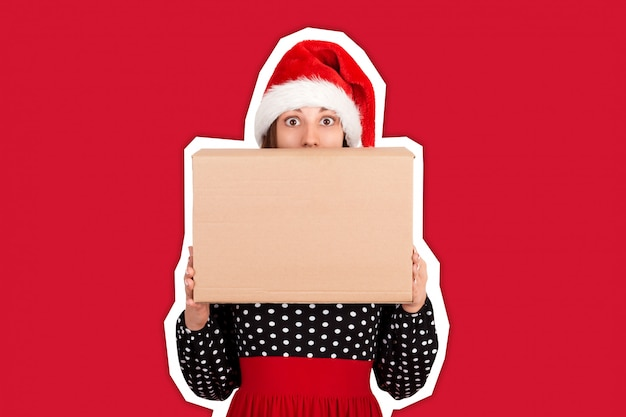 Shocked excited girl standing and holding big gift carton box. copyspace. magazine collage style  trendy color . holidays Premium Photo