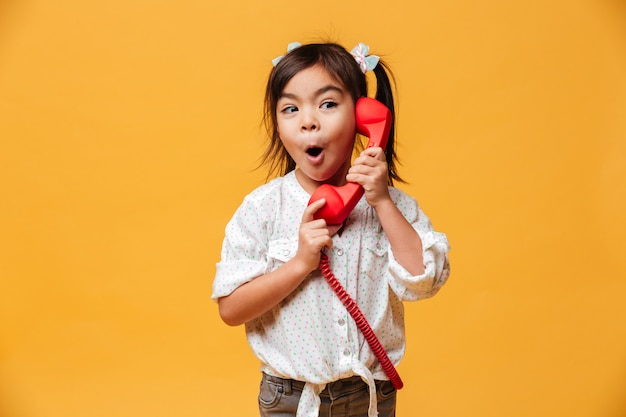 Shocked excited little girl talking by red retro telephone. Free Photo