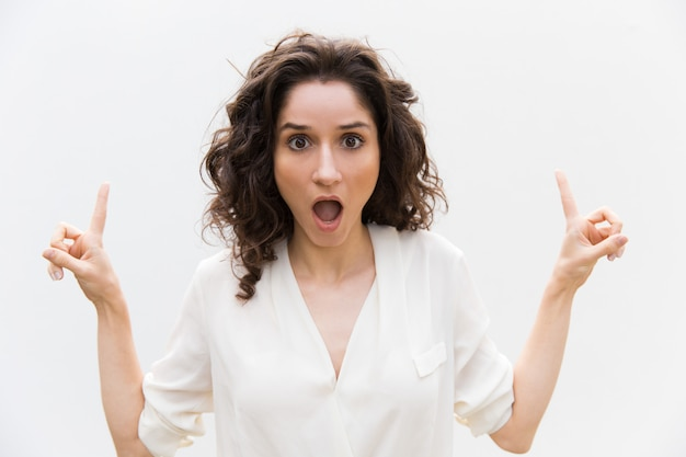 Shocked excited woman with open mouth pointing fingers up Free Photo