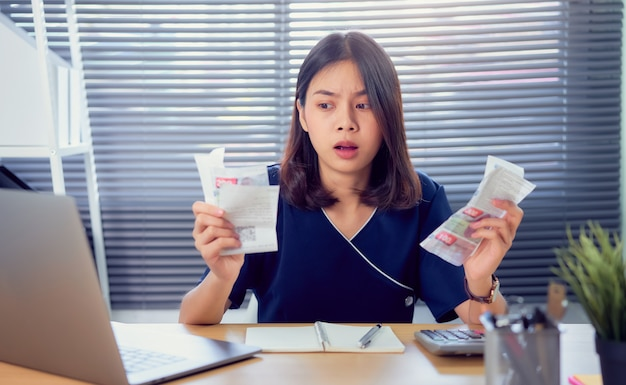 Shocked face asian woman hand holding expense bill and calculation about debt bills monthly at the table in home office. Premium Photo