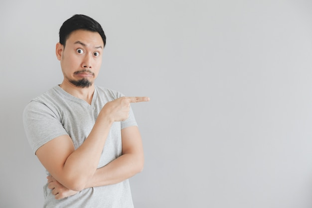 Shocked face of man in grey t-shirt with hand point on empty space. Premium Photo