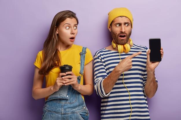 충격을받은 여성과 남성 친구가 스마트 폰 디스플레이를 가리키고, 모형 화면을 표시하고, 여성이 테이크 아웃 커피를 들고 데님 바지를 입고 스튜디오에서 나란히 서 있습니다. 무료 사진