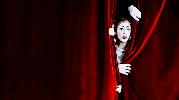 Shocked female mime artist peeking from red curtain Free Photo