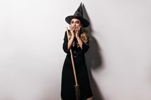 Потрясенная женская модель в костюме волшебника, позирующем на белой стене. крытый выстрел изумленной девушки-ведьмы, стоящей с испуганным выражением лица. Бесплатные Фотографии