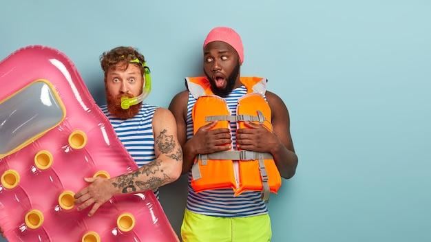 해변 항목과 함께 포즈를 취하는 충격 된 친구 무료 사진