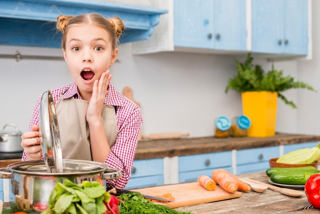 Shocked girl opening the lid of cooking pot in the kitchen looking at camera Free Photo