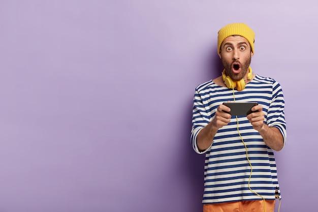 ショックを受けた感動の男のゲーマーは、スマートフォンでビデオゲームをプレイし、最新のテクノロジーに夢中になっています 無料写真