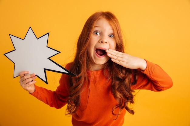 Сотрясенная маленькая девушка redhead держа пузырь речи. Бесплатные Фотографии
