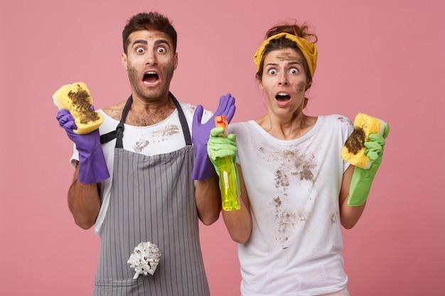 非常に汚れた冷蔵庫をきれいにする方法がわからないので、驚きの表情でカジュアルな服を着て家事をしているショックを受けた男性と女性。家事の恐怖と片付けをパニックで家族カップル 無料写真
