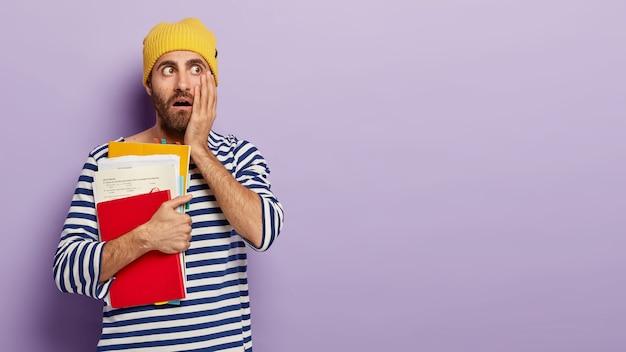 Studente maschio scioccato guarda con espressione terrorizzata, tiene la mano sulla guancia, trasporta blocco note e fogli, va a studiare, vestito con abiti casual sta al coperto sopra il muro viola Foto Gratuite